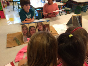 3rd graders, Grayson S., Charlotte W., and Juliette H., pose together as they sketch self-portraits